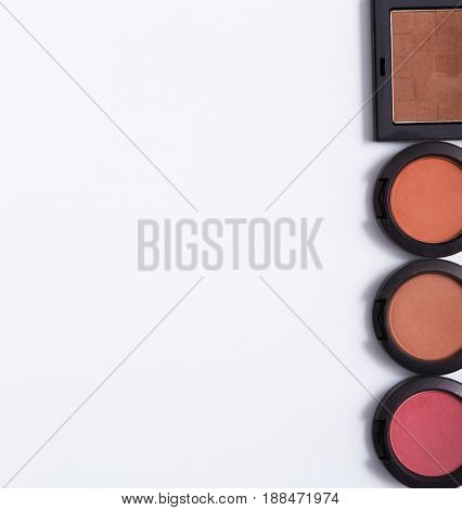 Makeup set, blushes border on white background. Top view, flat lay with copy space. Beauty tools palettes collection