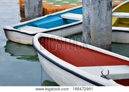 White rowboat moored near shore in the park.