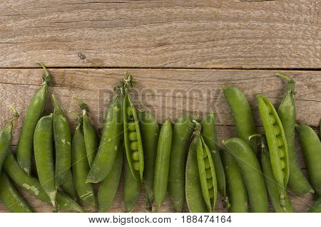 Gresh green peas on a wooden background