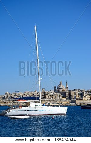 VALLETTA, MALTA - MARCH 30, 2017 - View of St Pauls Anglican Cathedral and the Basilica of Our Lady of Mount Carmel with a yacht in the foreground seen across the Grand Harbour from Sliema Valletta Malta Europe, March 30, 2017.