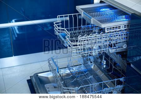 Empty Opened Dishwasher blue color. Kitchen dishwasher