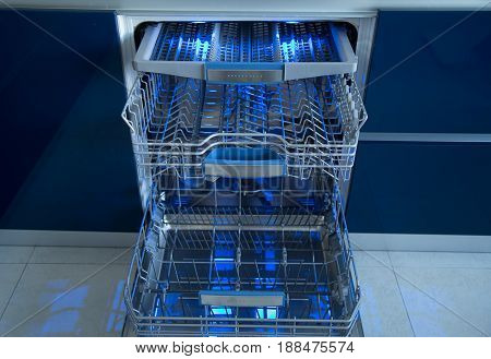 Empty Dishwasher with illumination. Kitchen  clean dishwasher.
