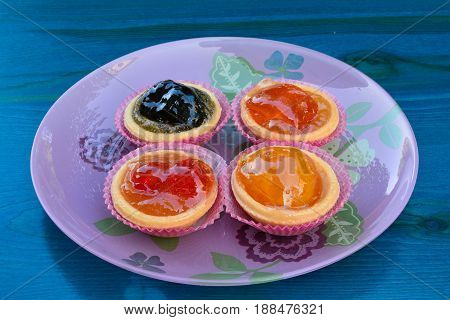 Punnets of dough filled in with various candied fruits served in pink glass plate on blue wooden table