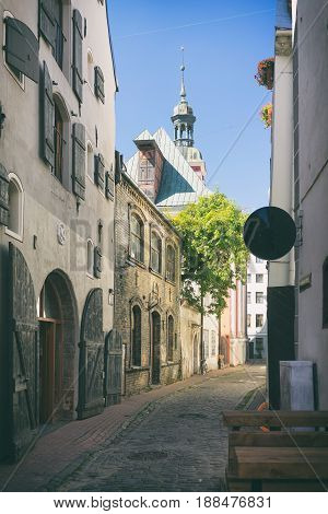A narrow ancient street with large warehouses and green trees near the synagogue in Riga on a summer day