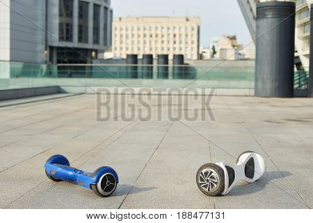 Two gyroboards on the pavement. White and blue hoverboards.
