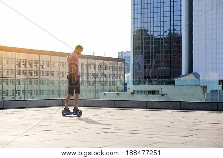 Man riding hoverboard. Guy on city background.