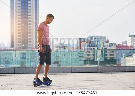 Man riding hoverboard, city background. Guy outdoors at daytime.