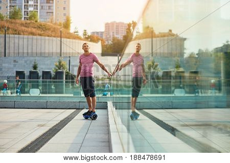Man on hoverboard. Young male outdoors at daytime. Life and tech.