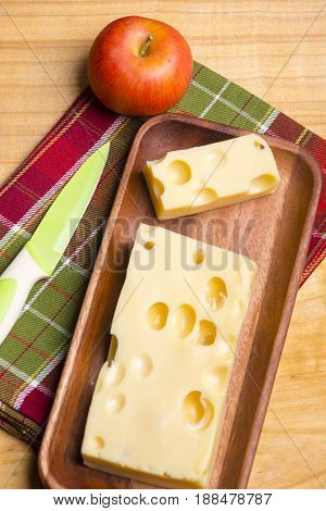 A Piece Of Emmethal Swiss Cheese Over A Wooden Rustic Plate, A Green Knife And A Fresh Appe.