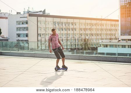 Man on a hoverboard. Young male, daytime city background. Inventions that change our life.