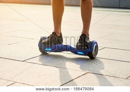 Legs of man on hoverboard. Person riding blue gyroboard. Best self balancing scooters.