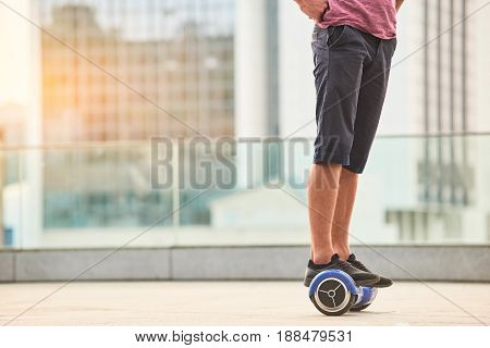 Legs of man on gyroscooter. Person riding hoverboard.