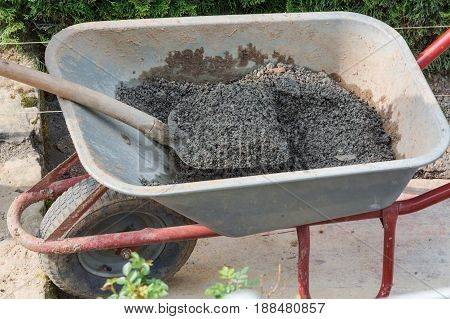 Wheelbarrow on a construction site filled with concrete.