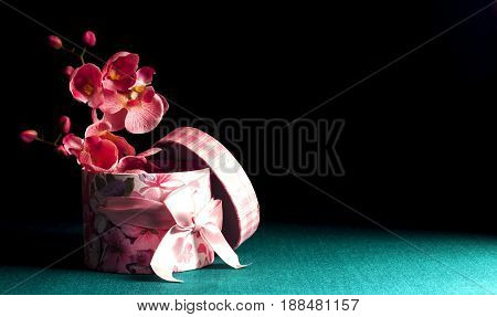 Decorative gift box with orchids on a dark green background