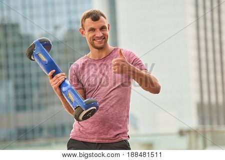 Man holding gyroboard, thumb up. Happy guy with gadget outdoors. Best hoverboard reviews.