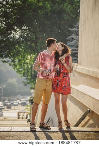 ODESSA, UKRAINE - OCTOBER 15, 2014: Happy young couple hugging and kissing outdoors summertime drinking cold Pepsi from glass bottles with straw.