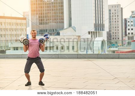 Man holding two hoverboards. Smiling guy on city background.
