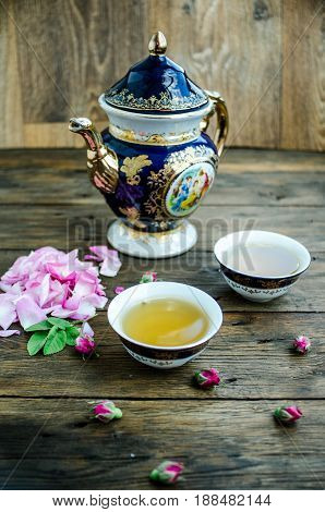 Cup Of Tea With Rose On White Wooden Table