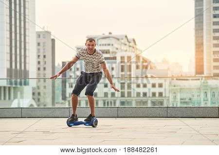 Guy riding hoverboard, city background. Young man on gyroscooter. Make friends with technology.