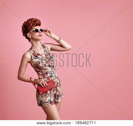 Fashion Model in Sexy Jumpsuit. Stylish Mohawk hairstyle, fashion Sunglasses, Summer Floral Outfit. Beauty Redhead Woman in Trendy Summer Dress. Glamour fashion Clutch. Playful Luxury Girl on Pink
