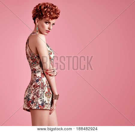 Fashion Beauty woman in Trendy Summer Dress. Stylish wavy hairstyle, fashion Makeup, Summer Floral Outfit. Glamour Redhead Model in Sexy Jumpsuit, fashion pose. Playful Girl, Luxury summer Accessories