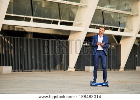 Young businessman on hoverboard outdoors. Guy wearing a suit.