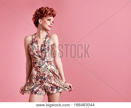 Fashion Model in Sexy Jumpsuit. Stylish Mohawk hairstyle. Beauty woman in Trendy Summer Dress, fashion Makeup, Summer Floral Outfit.Glamour Redhead, fashion pose. Playful Girl, Luxury summer Accessories