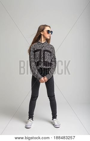 Portrait of young beautiful girl with black sunglasses over gray background. woman dressed in black T-shirt, jeans and white shoes