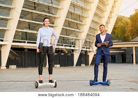 Business people on hoverboards. Man and woman smiling outdoors. Society of the future.