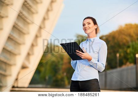 Businesswoman with clipboard smiling. Happy caucasian female outdoor. How to find dream job.