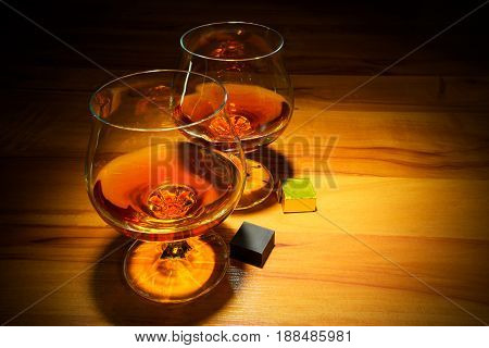 Two scotch glasses and chocolate bars on wooden background. Bourbon snifters or old fashioned whiskey.