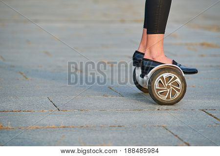 Legs on gyroscooter, side view. Hoverboard and pavement.