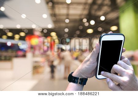 Female hands use smartphone in shopping mall.