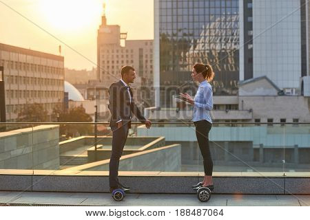 Business people on city background. Man and woman on hoverboards. How to become successful.