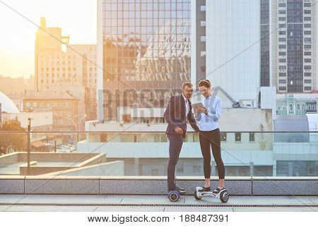 Businessman and woman on hoverboards. People in the city. Society, business and technologies.