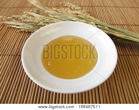 Rice syrup in bowl and rice panicles