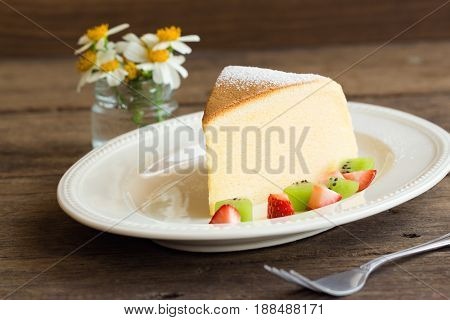 Homemade Japanese cheesecake. Delicious soft cheesecake fluffy,lite and soft.  Japanese cotton cheesecake serve with sparkling icing fresh fruit : kiwi and strawberry. Japanese cheesecake on white plate put on rustic wood table for your relax time.