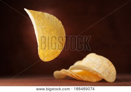 Crispy Potato Chips On A Wooden Background. Chips In The Air.