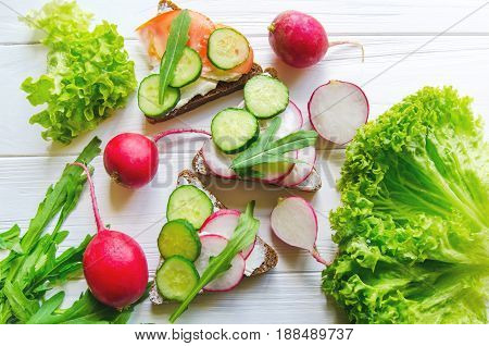 Sandwiches Of Wheat Brown Bread With Cucumbers And Radish With Leaves Of Fresh Green Salad On White