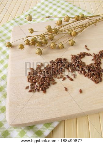 Linseeds or flaxseeds and flax on wooden board