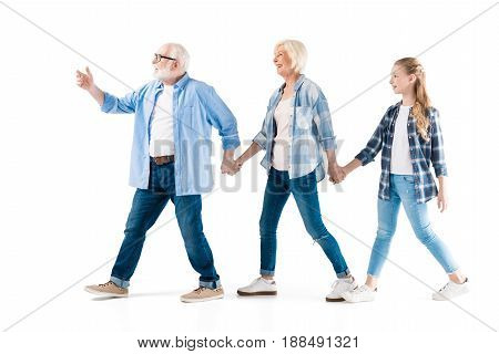 Happy Grandfather, Grandmother And Granddaughter Walking And Holding Hands Together Isolated On Whit