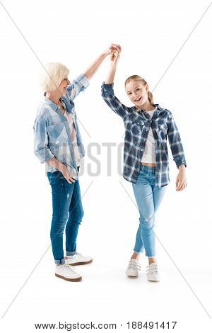 happy grandchild dancing with grandmother isolated on white in studio