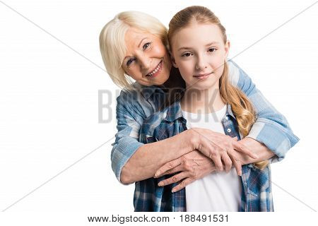Portrait Of Grandmother And Granddaughter Embracing Isolated On White In Studio