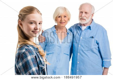 Happy Grandchild Looking At Camera With Grandfather And Grandmother Behind Isolated On White In Stud