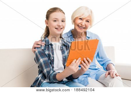 Grandmother And Grandchild Using Digital Tablet And Sitting On Sofa Isolated On White