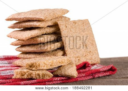 stacked crisp bread on a wooden table isolated on white background.