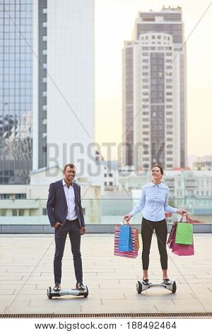 Couple with shopping bags. Man and woman riding hoverboards. Life, business and wealth.