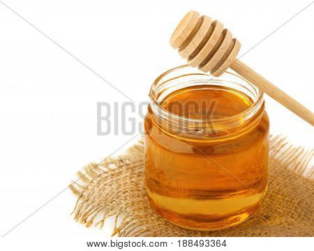Honey in jar with a wooden spoon isolated on white