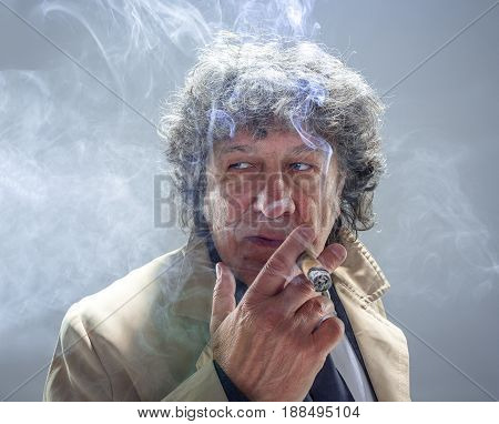 The senior man in cloak with cigar as detective or mafia boss. Studio shot on gray in retro stile