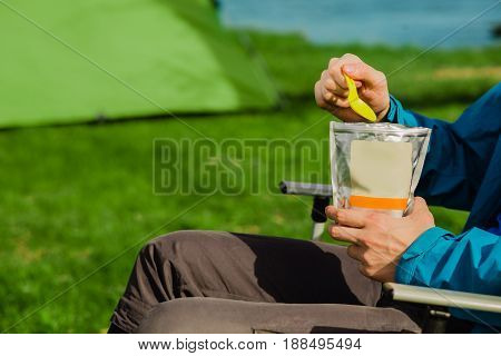 Hand holding freeze dried food , enjoy a tasty food during the camping holidays. In the background tourist tent and equipment for outdoor activities.